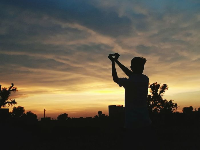 Silhouette man shaping heart against sky at sunset