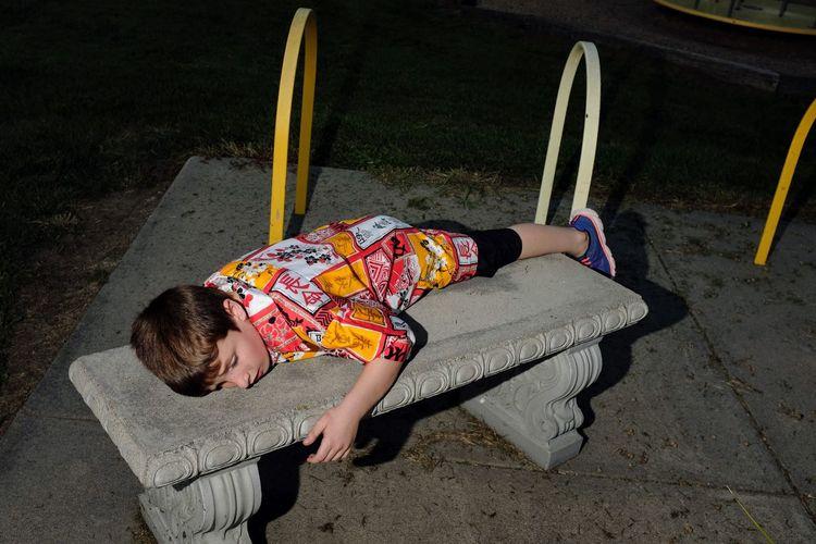 Boy lying on bench at playground