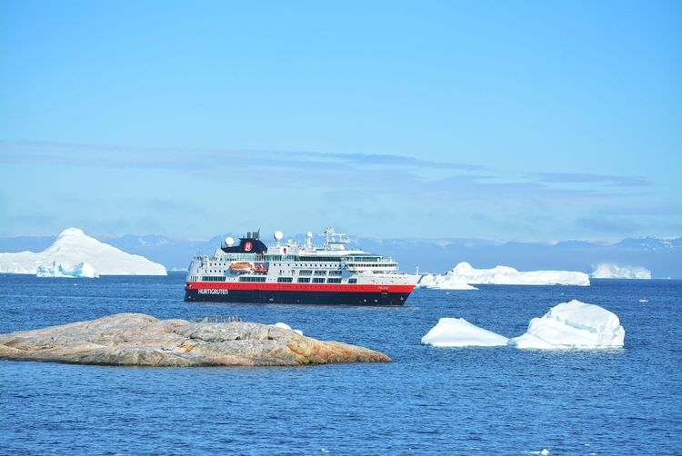 Ilulissat, Greenland, July | UNESCO world heritage site | impressions of Jakobshavn | Disko Bay Kangia Icefjord | huge icebergs in the blue sea on a sunny day | climate change - global warming | Hurtigruten anchored in the bay Greenland Travel Destinations UNESCO World Heritage Site Iceberg Icebergs Ice Sea White Nature Day Scenics - Nature Outdoors Water Climate Change Global Warming Hurtigruten Anchored Cruise Ship Travel Ship Mode Of Transportation Nautical Vessel Passenger Craft Sailing Transportation