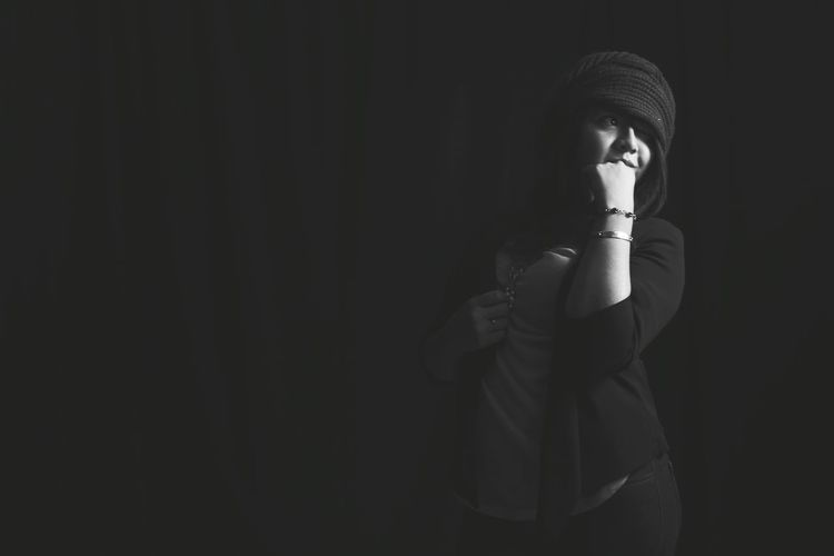 Beautiful young woman wearing knit hat against black background
