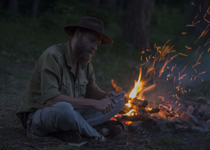 Man Carving Wood While Sitting By Campfire During Sunset
