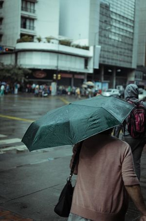 Rainy Walk Architecture Building Exterior Built Structure City City Life Focus On Foreground Lifestyles Men Monsoon Outdoors People Protection Rain Rainy Season Real People Rear View Street Streetphotography Umbrella Walking Wet