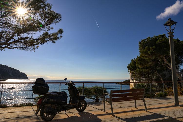 People sitting on street by sea against sky