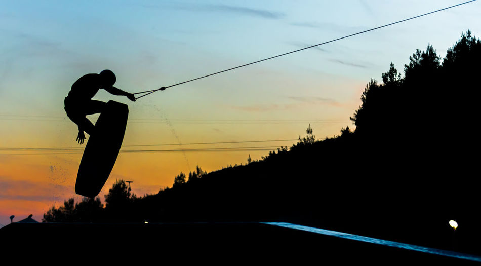 Low angle view of silhouette person wakeboarding in mid-air against sky during sunset