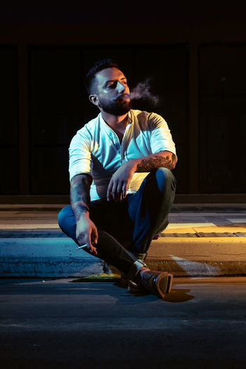 Young man looking away while sitting on road in city