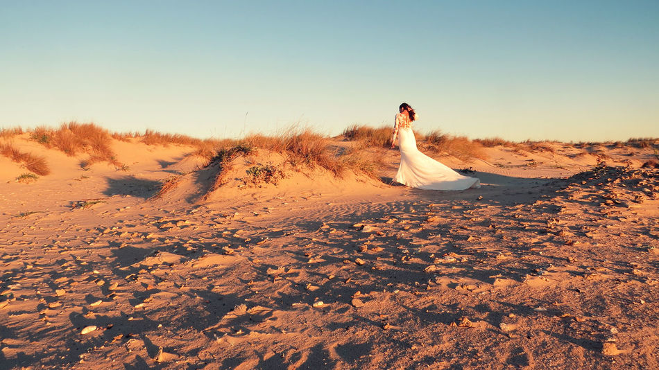 EyeEmNewHere Dress Wedding Wedding Photography Adult Beauty In Nature Bride Clear Sky Day Desert Full Length Leisure Activity Lifestyles Marry Nature Outdoors People Real People Rear View Sand Sand Dune Sky Standing Sunlight Wedding Dress Women