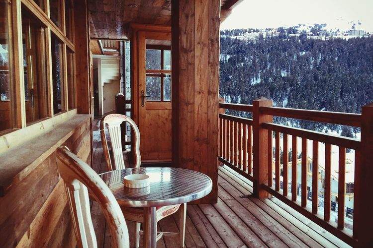 Chairs and table in building balcony during winter