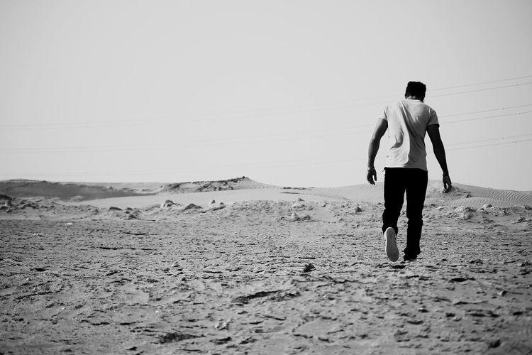 Rear View Of Man Walking In Desert Against Clear Sky