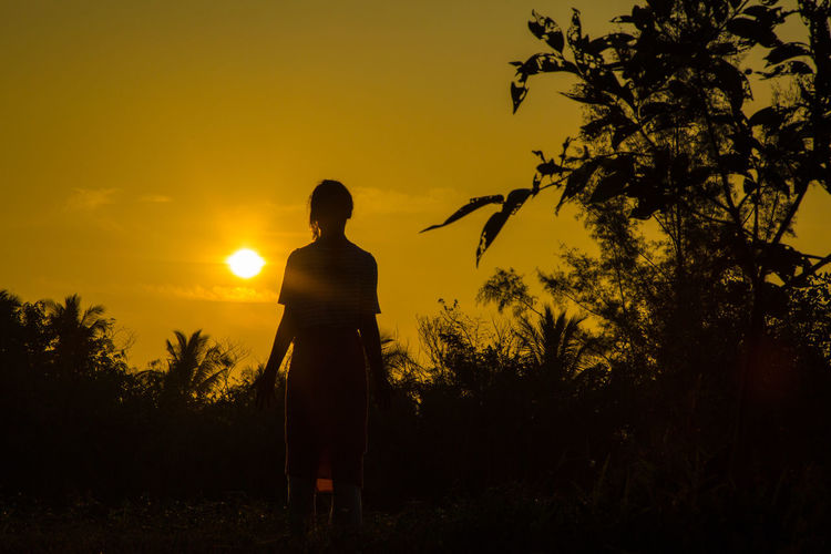 Silhouette of man looking at sunset