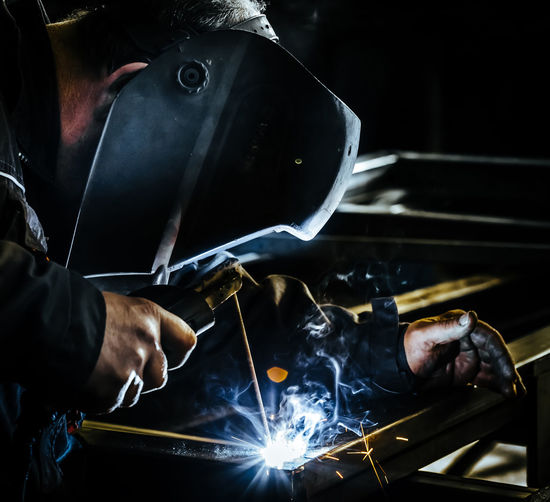 Professional mask protected welder man working on metal welding and sparks metal. Construction Craftsman Industrial Industry Man Sparkle Welding Worker Equipment Factory Fire Manufacturing Equipment Mask Metal Protection Safety Spark Sparks Steel Tool Weld Welder Welding Mask Welding Sparks Welding Work
