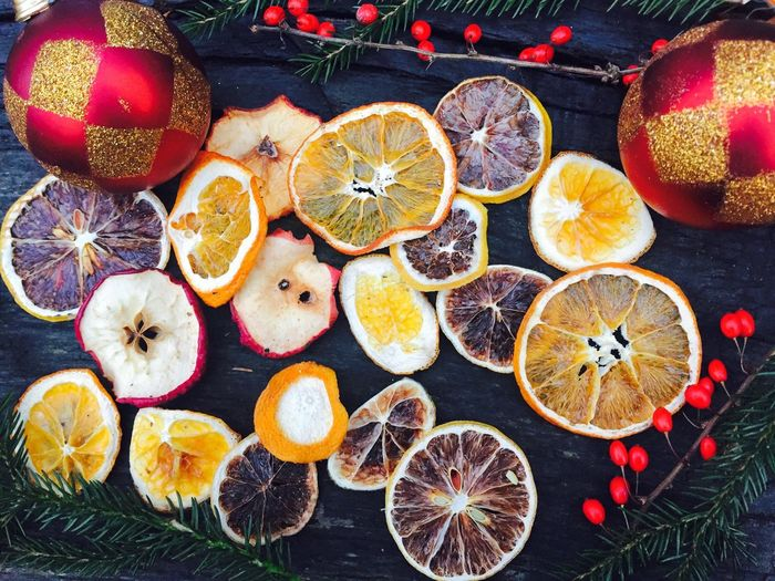 Christmas spirit like dry oranges,dried apples,cinnamon,pine cone branches and globes