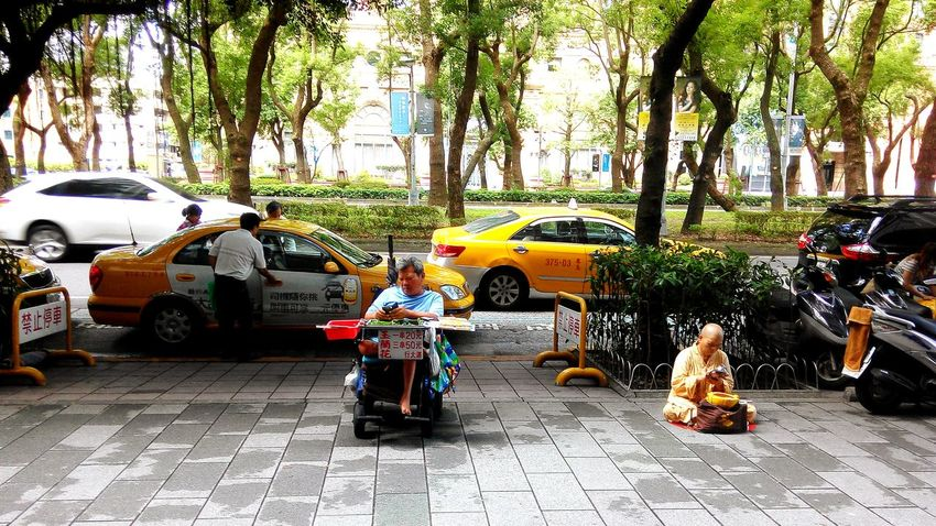 Disabled Person Selling Flowers Beside The Road & Buddhist Monk Using Mobile Phone Connection And Communication The View And The Spirit Of Taiwan 台灣景 台 Transportation Land Vehicle Car Mode Of Transport Street Road Tree Parking Men Full Length Stationary Day Outdoors City Life Abundance Large Group Of Objects Internet Addiction