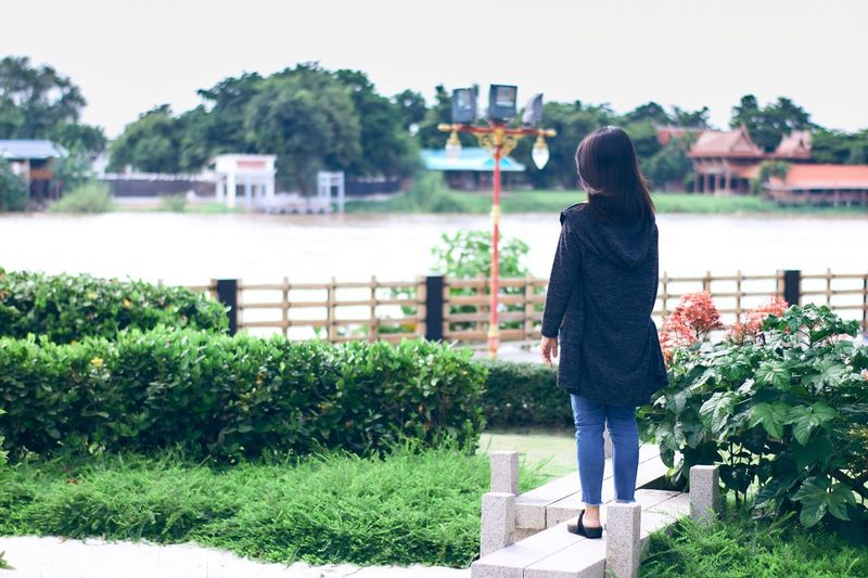 Asian girl looking at river in Thailand. One Person Outdoors Women Day Standing Plant Nature Tree Bokeh Photography Beautiful Relaxing Girl Portrait Freshness Asian  Leisure Activities Garden River Landscape Scenic View Beauty In Nature Mix Yourself A Good Time Mix Yourself A Good Time