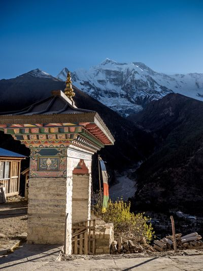 Traditional building by mountains against clear sky