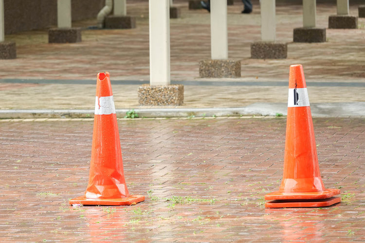 CONSTRUCTION CONE ON WET ROAD Architectural Column Architecture Bollard Building Built Structure City Close-up Cone Day Focus On Foreground Guidance Nature No People Orange Color Outdoors Plastic Protection Red Rules Safety Security Traffic Cone