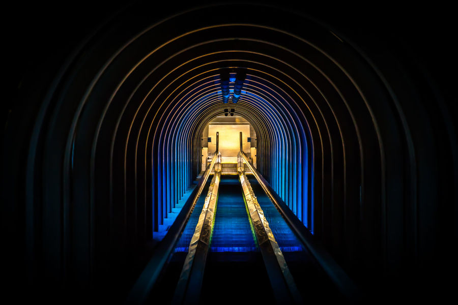 Architectural Detail Blue Diminishing Perspective Downwards Escalator Illuminated Indoors  Night The Way Forward Let's Go. Together.