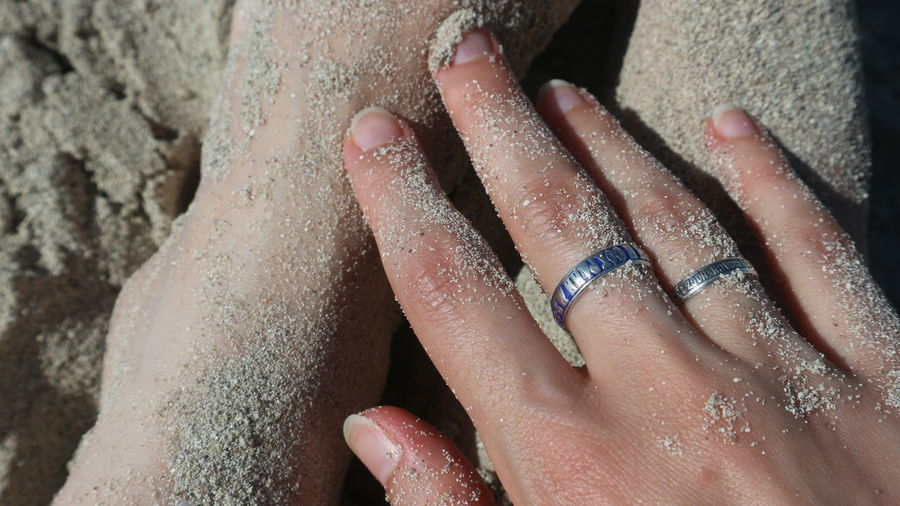 Cropped hands of woman on sand