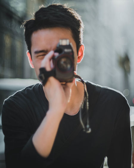 Young Adult Front View One Person Portrait Real People Headshot Young Men Lifestyles Casual Clothing Waist Up Standing Focus On Foreground Men Camera - Photographic Equipment Leisure Activity Photography Themes Activity Photographing Day Obscured Face Filmcamera Focus My Best Photo