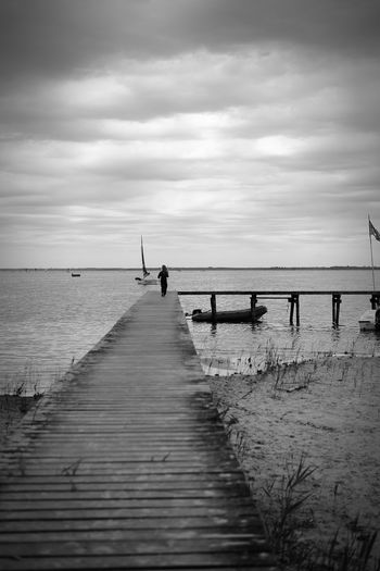 Rear view of girl walking on pier over sea