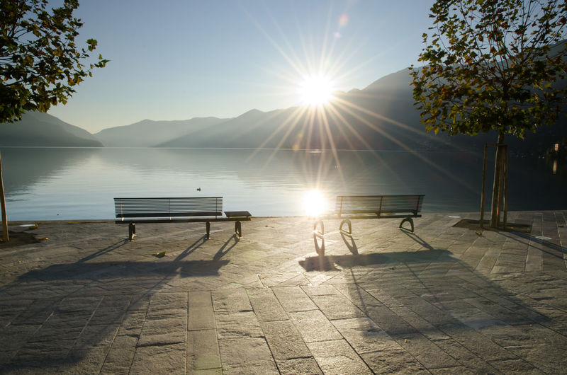 Bench on waterfront with Sunbeam in Ascona, Switzerland. Bench Reflection Backlit Beauty In Nature Day Lake Mountain Nature No People Outdoors Scenics Sea Shadow Sky Street Sun Sunbeam Sunlight Sunset Swiss Alps Tranquil Scene Tranquility Tree Walkway Waterfront