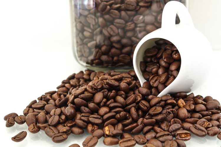 Close-up of roasted coffee beans with pitcher and jar against white background