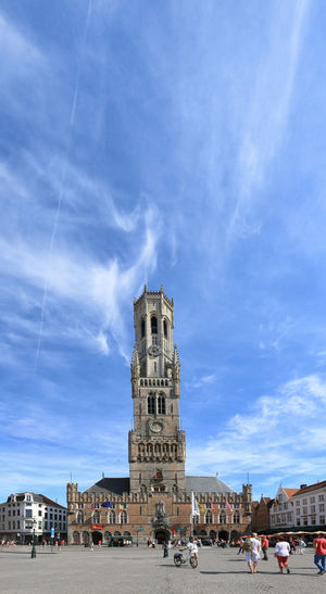 Bruges, Belgium - July 7, 2017: Tourists walinkg in front of the Belfry Tower in the market square in the center of Bruges, a beautiful medieval town in Belgium Beer Belgium Brugge Chocolate Dijver Canal Duvel Flanders Panoramic View Provinciaal Hof West Flanders Aerial View Belfry Tower Bikes Bruges Europe Flower French Fries Holland Market Square Medieval Town Mussels