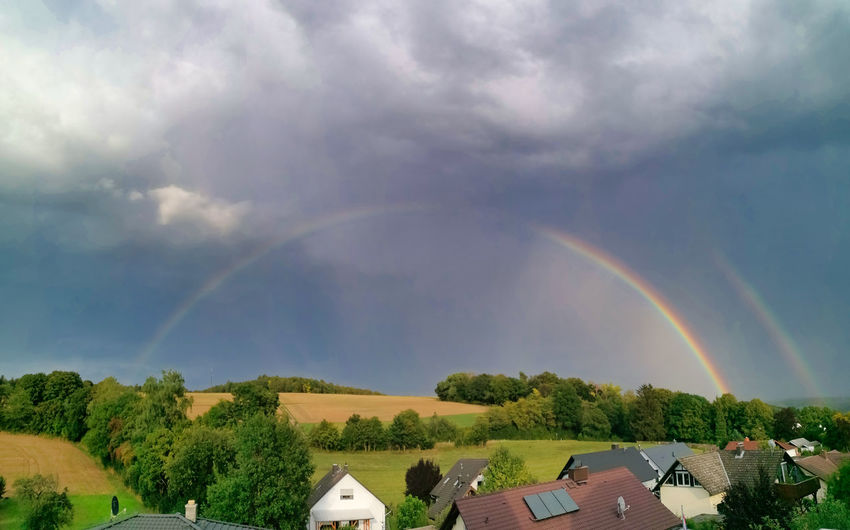 Scenic view of rainbow over buildings against sky