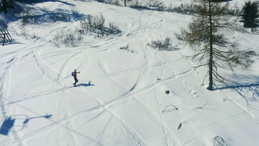 High angle view of man skiing on snowy field during sunny day