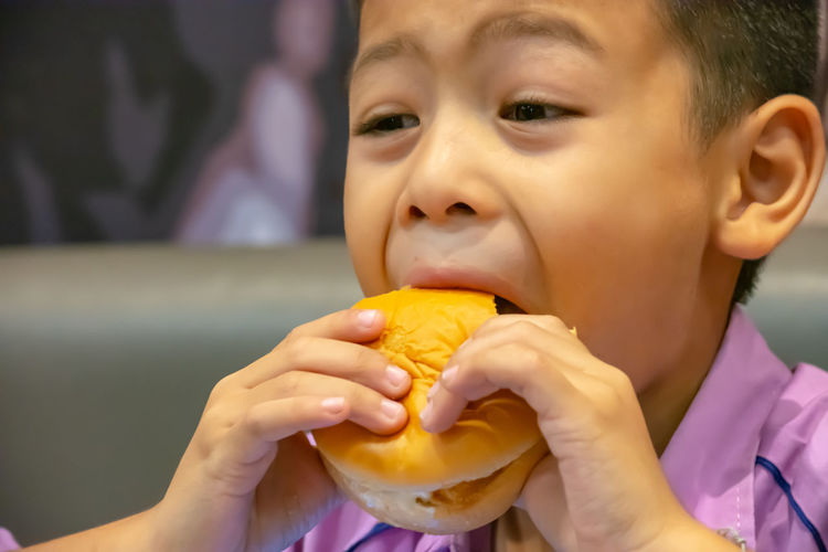 Close-up of boy looking away while eating burger