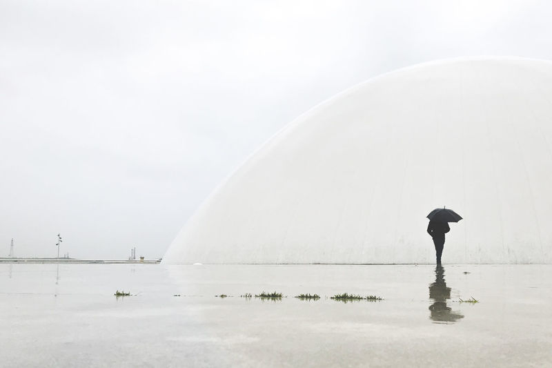 Side view of man with umbrella standing in lake against sky during rainy season
