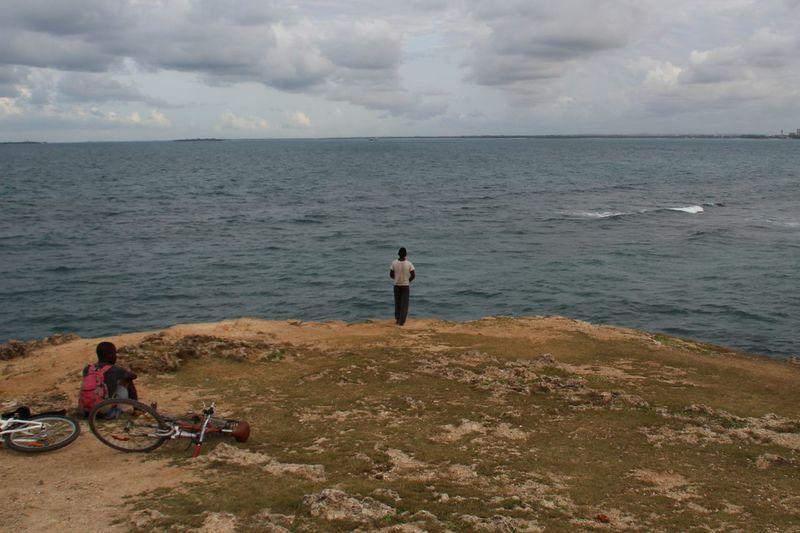 Rear View Of Men Beach Against Sky