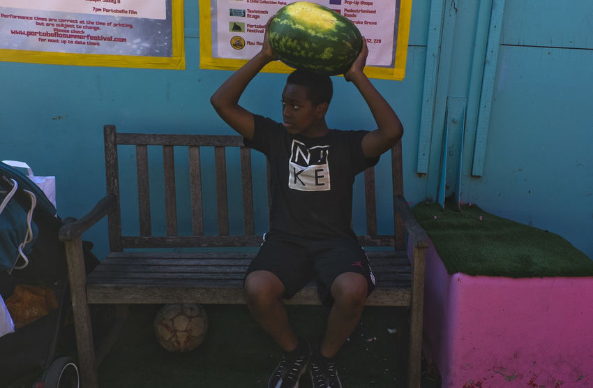 A boy lifting a watermelon in Portobello Road on 8th of July 2018 in London, United Kingdom. Portobello Market is probably the world's best known market. Next after the Antiques comes the fruit and vegetable section of the market. (photo by Lorenzo Grifantini/In Pictures ) Market Notting Hill Portobello Market Boys Fruit Rbkc Sitting Teenage Boys Watermelon