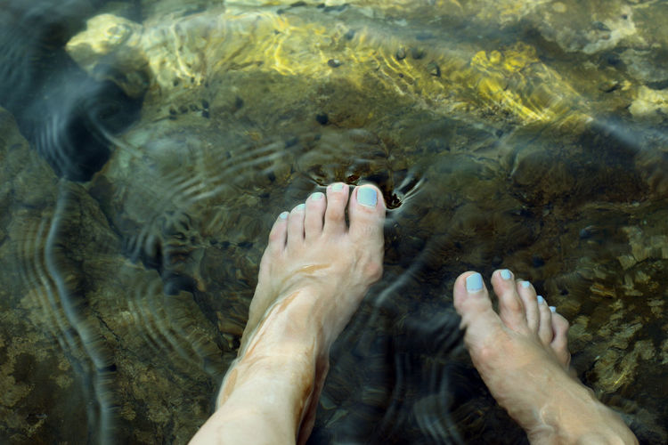 Low section of woman legs in water