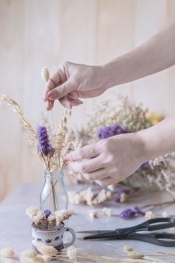 Cropped Hands Of Mature Woman Arranging Flowers In Vase On Table