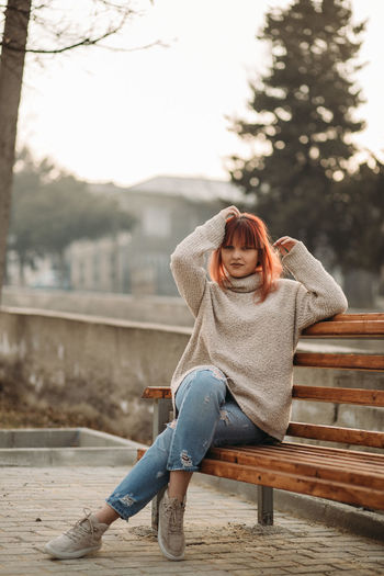 One Person Full Length Sitting Casual Clothing Real People Leisure Activity Adult Lifestyles Women Bench Jeans Seat Mid Adult Nature Relaxation Looking At Camera Day Young Adult Outdoors Hairstyle Beautiful Woman Warm Clothing Arms Raised