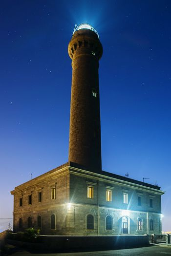 Low Angle View Of Illuminated Lighthouse Against Clear Sky At Night