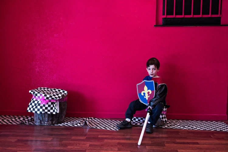 Full length portrait of boy in costume sitting against pink wall