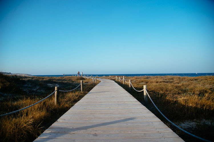 Boardwalk On Grass Against Clear Blue Sky