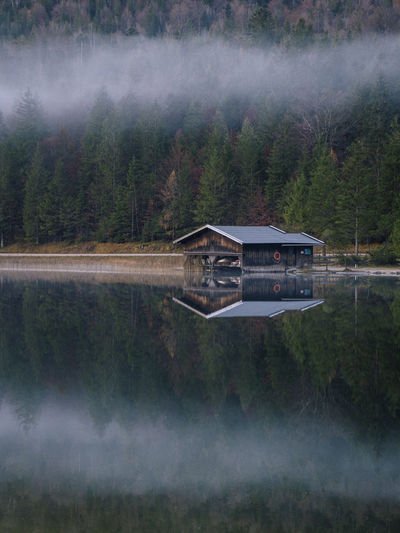 View of hut by lake against misty forest