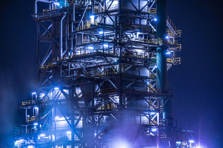 Low angle view of illuminated industry against sky at night