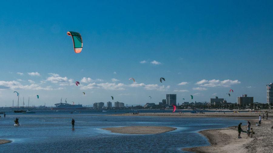 People on beach in city against sky