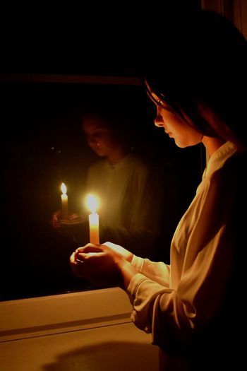 Girl holding lit candle in darkroom