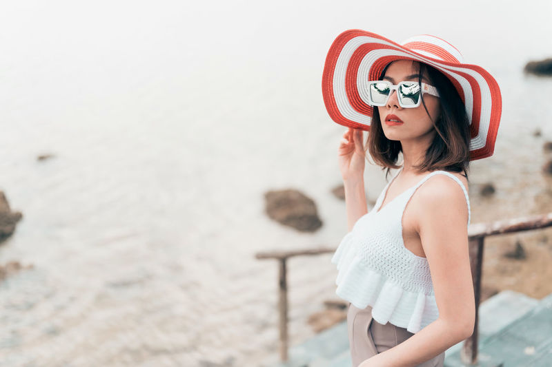 Side view of young woman wearing sunglasses standing against sea