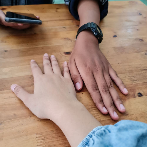 High angle view of hands on table