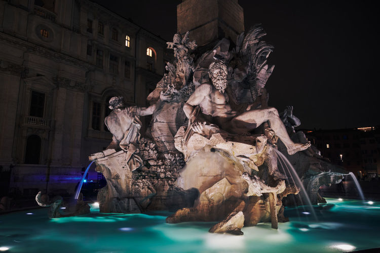 Statue of fountain in city at night
