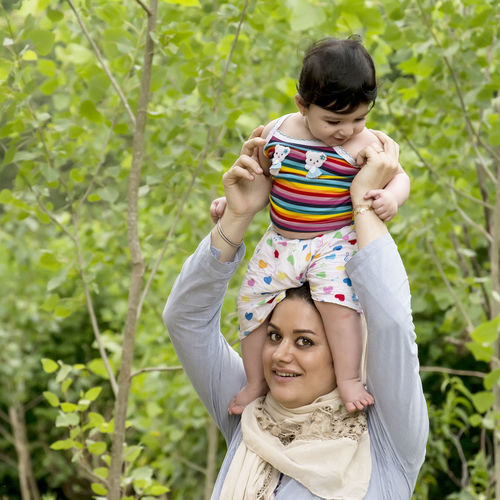 Young Muslim mother holding a little baby overhead enjoying in outdoor area, happiness expression concept Family Muslim Mother Relationship Casual Clothing Caucasian Child Childhood Emotion Enjoying Life Front View Happiness Innocence Leisure Activity Lifestyles Looking At Camera Outdoors Parent People Plant Portrait Real People Smiling Togetherness Two People Women