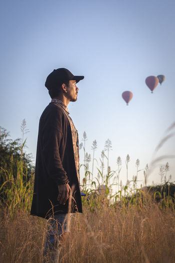Man looking away while standing on field with air balloons in the sky