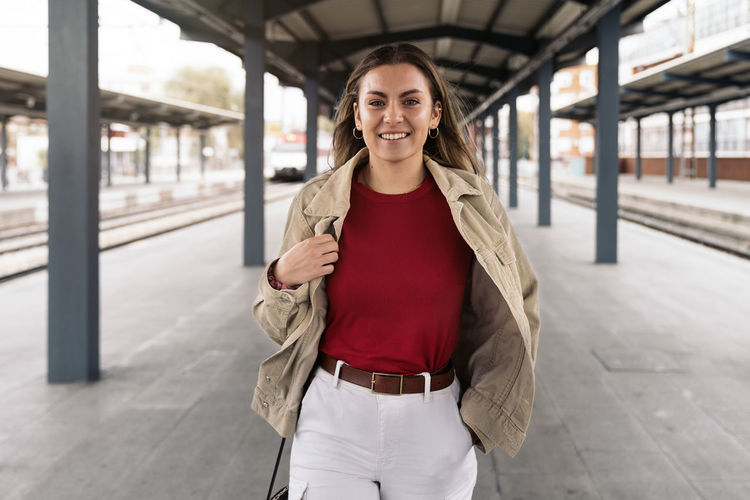 Portrait of smiling woman standing at railroad station
