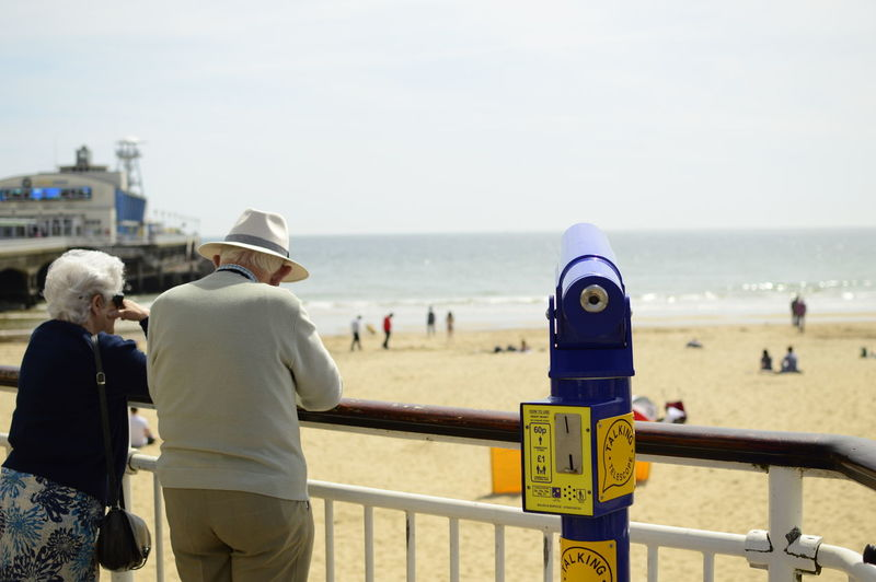 Senior Couple Standing By Coin-Operated Binoculars At Beach On Sunny Day