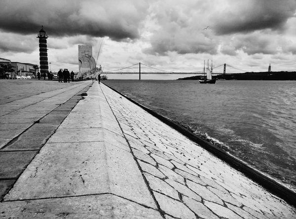 Monochrome Photography Lisbon Lisboa Portugal Lisbon - Portugal City Water Connection Suspension Bridge River Cloud - Sky Architecture Waterfront Padrão Dos Descobrimentos Discoveries Monument Boat Built Structure Day Tagus River Rio Tejo